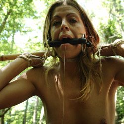 Outdoors bdsm training. Her BDSM master, wearing a gag mask, approaches with a single tail whip. He goes to work on her bare naked titties.
